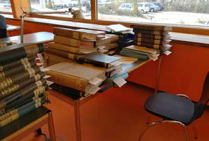 Photo of a desk stacked full of books and files in the State Archive Hamburg reading room.